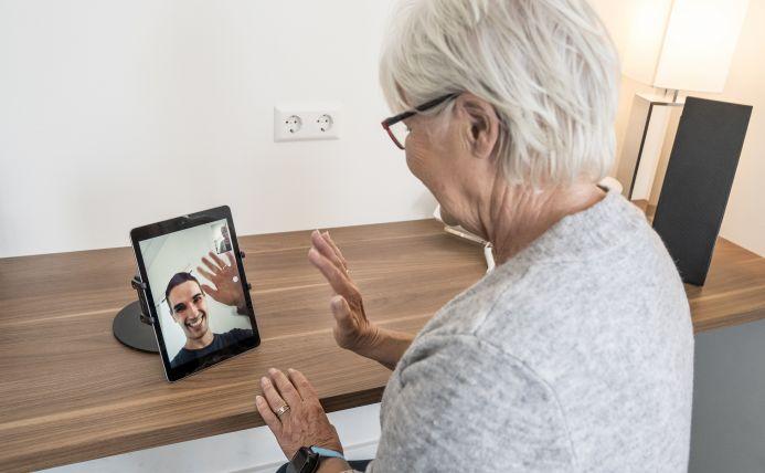 Oudere vrouw is aan het beeldbellen met een jonge man.