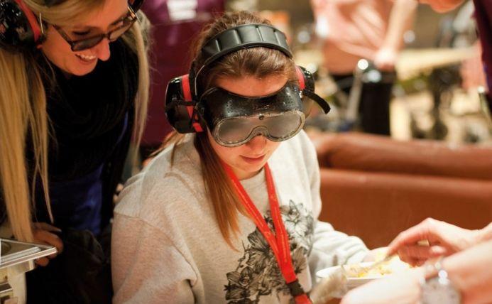 Vrouw met aangepaste duikbril en koptelefoon op, in een rolstoel, ervaart hoe het is om oud en zorgafhankelijk te zijn.