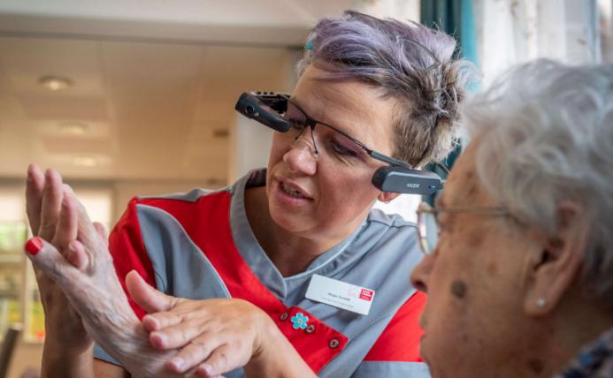 Zorgverlener gebruikt Smart Glass bij het onderzoeken van hand van een mevrouw.