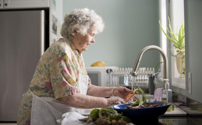 Oudere vrouw in de keuken wast groenten af onder de kraan.