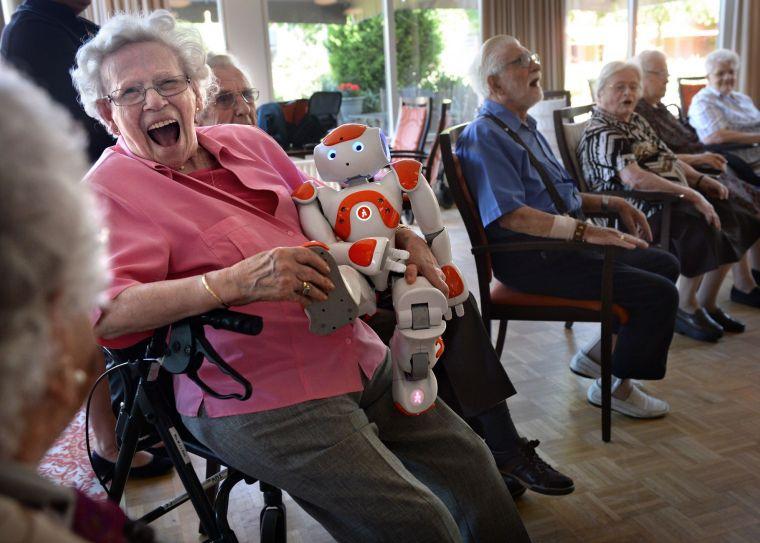 Oudere vrouw lacht met zorgrobot in de armen.