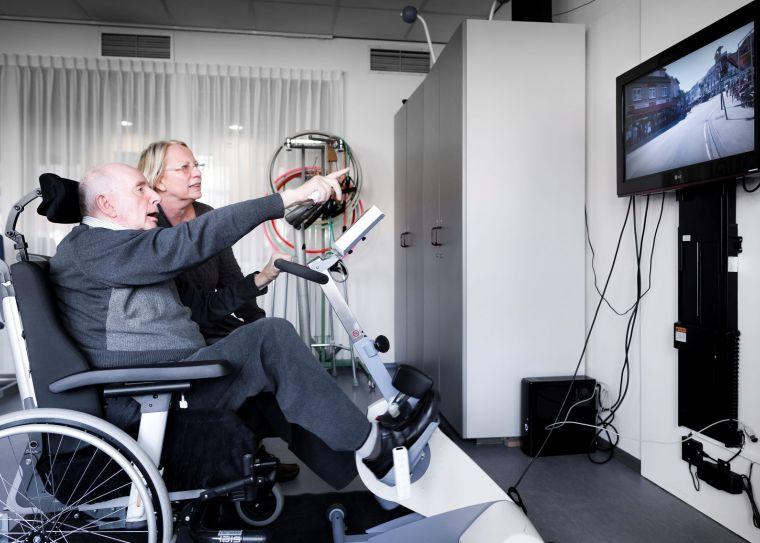 Oudere man op een fietstrainer wijst naar het beeldscherm voor hem.