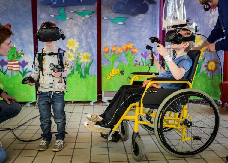Twee kinderen, een ervan in een rolstoel, hebben een VR-bril op.