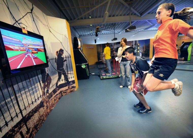 Meisje springt enthousiast mee met beelden op beeldscherm.