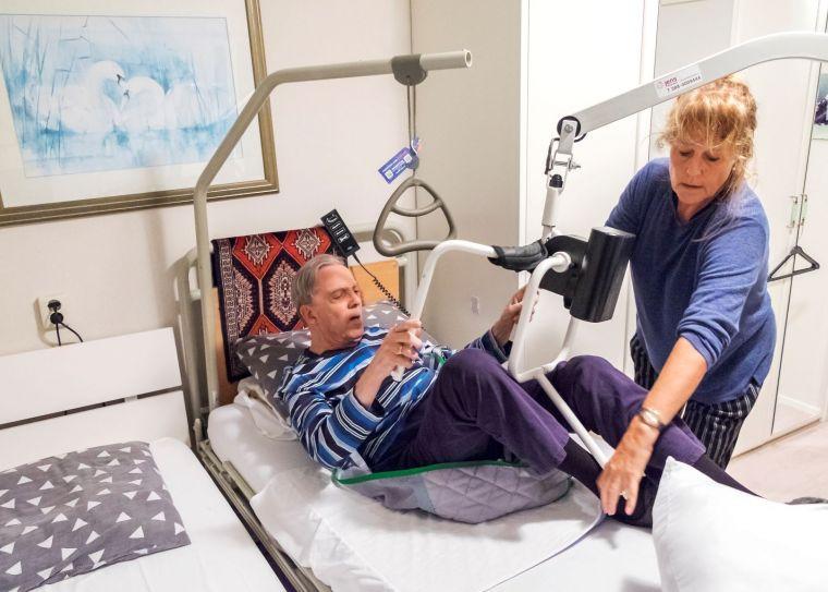 Zorgverlener helpt patiënt in bed met een tilhulp.