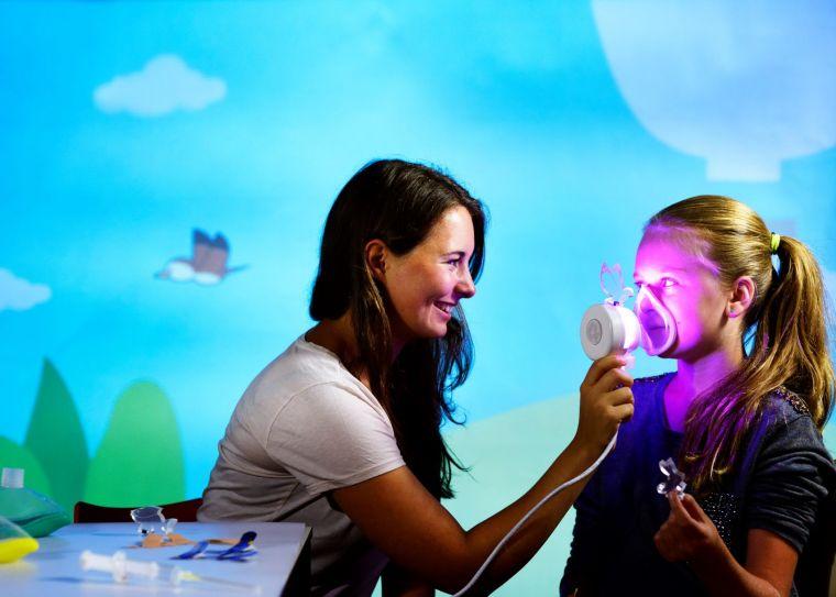 Vrouw helpt meisje met een felgekleurd masker vlak voor een operatie.