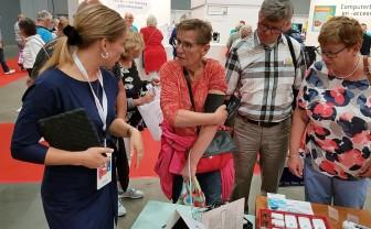 vrouw probeert bloeddrukmeter uit en anderen kijken daarnaar