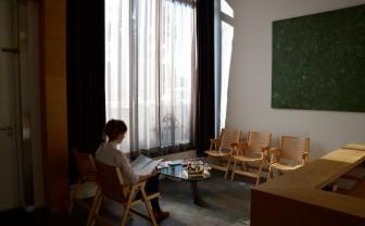 vrouw zit in voorkamer van huis, ingericht als wachtkamer
