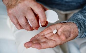 Twee oudere handen met in de ene hand een doosje pillen en in de andere hand 1 pil