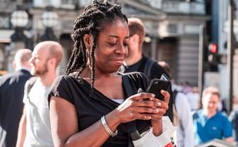Vrouw op straat kijkt op smartphone