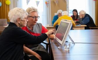Een zorgverlener helpt een oudere vrouw op de Braintrainer.