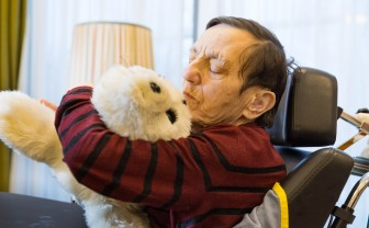 Oudere man knuffelt zeehond Paro, een robot in de zorg