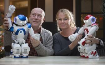 Bart Meussen en Mirjam van Blanken met twee Zora-zorgrobots