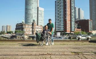 Een jongen duwt een andere jongen in een rolstoel over een plein in een stad.