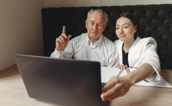 Oudere man en jonge vrouw zitten samen te beeldbellen achter een laptop.
