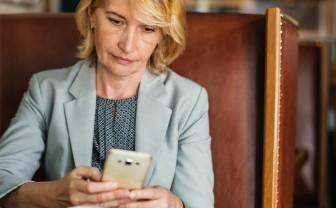 vrouw kijkt op mobiele telefoon