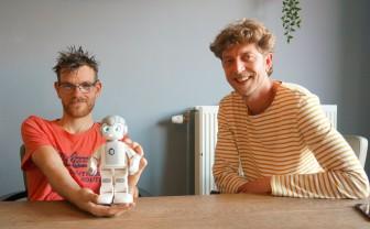 Cliënt Rick houdt robot Maatje vast en naast hem zit coördinator innovatie Martijn Schep.