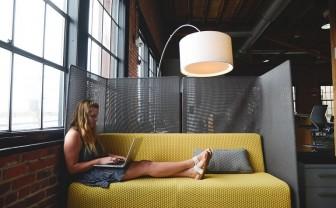 vrouw zit op bank met laptop