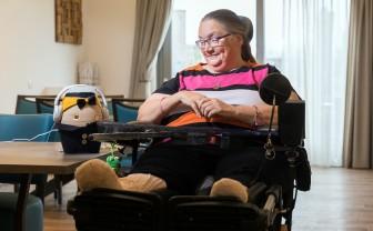 vrouw in rolstoel kijkt naar zorgrobot tessa