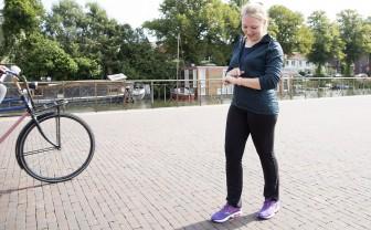 Vrouw in sportoutfit kijkt op smartwatch tijdens het lopen.