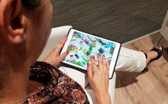 Vrouw zit met tablet op schoot spelen van de dementiegame