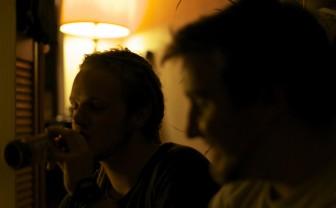 Twee jonge mannen waarvan er een fles bier drinkt