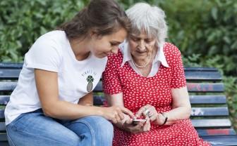 Student zit op bankje met oudere dame en helpt met telefoon