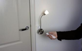 Een hand heeft een afstandsbediening vast en richt deze op een lamp aan de muur.
