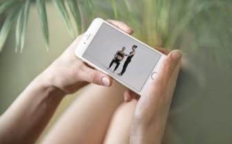 Een vrouw houdt een smartphone op haar schoot en bekijkt de app van Carinwear