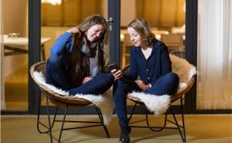 Twee jonge vrouwen kijken samen op een smartphone