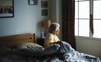 Oudere vrouw zit in bed en kijkt naar buiten.