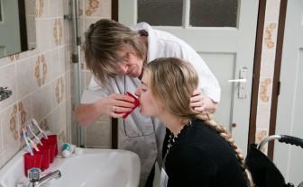 Een zorgverlener helpt een patiënt in een rolstoel met drinken.