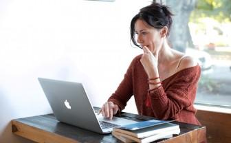 Bezorgde vrouw zit achter laptop