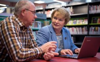Oudere vrouw krijgt PC hulp van oudere heer.