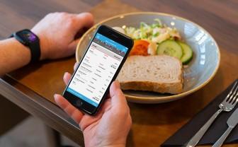 Persoon gebruikt mijn eetmeter app om voedingsmiddelen op bord te registreren