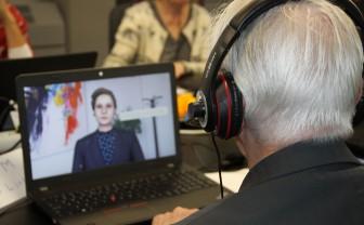 Een man zit achter een computer en heeft een koptelefoon op. Hij kijkt naar het scherm en speelt de oefendokter.