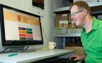 Een jongen met Down zit achter een computer. Hij bekijkt de site van Ik ben geen kind meer