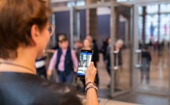 Een vrouw houdt een smartphone in haar hand. De smartphone is gericht op een groep mensen.