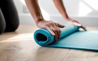 Vrouw rolt yogamatje uit