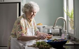 Oudere vrouw wast groenten in de keuken.