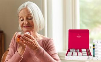 Oudere vrouw drinkt kopje thee met leefstijlmonitoring sensoren naast zich