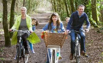 Een gezin fietst door het bos van hun gezonde gemeente.