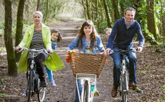 gezin fietst door het bos