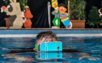 jongen met vr-bril op in zwembad