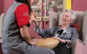 Lachende oudere vrouw en verpleegster raken beiden CRDL aan en houden elkaars andere hand vast
