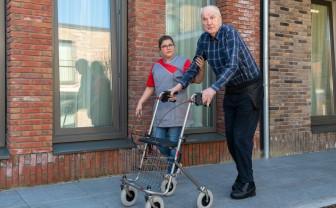 oudere man met heupairbag en zijn verzorger lopen op straat