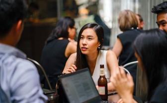 Vrouw probeert naar gesprek te luisteren terwijl achter haar allemaal mensen overleggen.