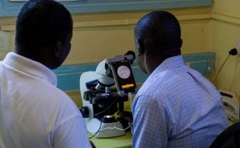 Twee mannen kijken naar een smartphone gemonteerd op een microscoop om malaria te ontdekken