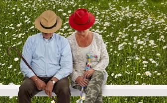 Een ouder stel zit op een bankje met wandelstokken met wandelstok accessoires.