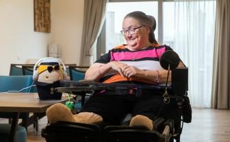 Vrouw in een rolstoel luistert naar Tinybot Tessa die op tafel staat.